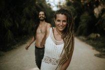 Ritratto di donna sorridente con dreadlocks che tiene per mano uomini e guarda la macchina fotografica sulla strada tropicale tra le palme — Foto stock