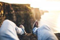 Legs of man wearing jeans sitting on coastal cliff — Stockfoto