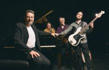 Gruppe von Männern unterschiedlichen Alters posiert mit verschiedenen Instrumenten auf der Bühne — Stockfoto
