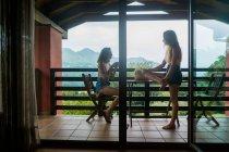 Vista laterale di donne che mangiano caffè sulla terrazza — Foto stock