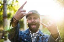 Portrait d'homme expressif en cap et denim jacket criant à la caméra et gesticulant signe rock. — Photo de stock