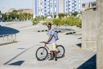 Hombre de pie con la bicicleta - foto de stock