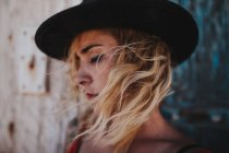 Romantic blonde woman in hat with septum and windy hair looking down — Stock Photo