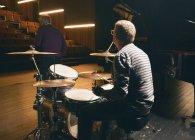 Vista posteriore dell'uomo che gioca i tamburi in fase — Foto stock