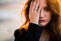 Портрет женщины, закрыв один глаз с руки и глядя на камеру — стоковое фото