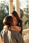 Portrait de copine souriante embrassant autour de cou de copain — Photo de stock