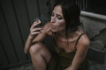 Portrait of brunette woman smoking cigarette and looking away pensively — Stock Photo