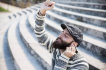 Portrait of bearded man with eyes closed holding hand up and listening to music. — Stock Photo