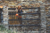 Girl with pumpkin basket posing on fence — Stock Photo