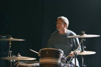 Mature man in  sitting on stage and playing drums while smiling away — Stock Photo