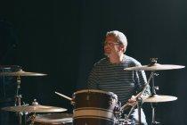 Uomo maturo in seduta sul palco e suonare la batteria mentre sorridente distanza — Foto stock