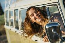 Улыбающаяся девушка, выходящая из винтажного фургона и смотрящая в боковое зеркало — стоковое фото