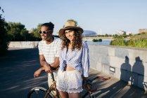 Coppia appoggiata in bicicletta al parco urbano — Foto stock