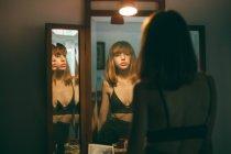 Rückansicht des junge Frau im schwarzen BH stehen im Spiegel — Stockfoto