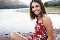 Menina olhando para câmera no lago de montanha — Fotografia de Stock