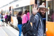 Portrait of bearded man in hat carrying backpack and waving hand at camera — Stock Photo