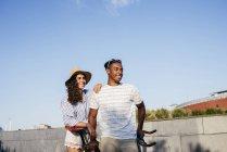 Couple penchée sur le vélo et en regardant de côté — Photo de stock