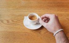 Colpo di raccolto della mano maschio che tiene piccola tazza di caffè espresso al tavolo di legno bianca — Foto stock
