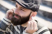 Portrait of pensive bearded man putting earphones — Stock Photo