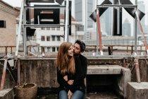 Чудова пара, сидячи на даху з видом на великий місто на тлі. — стокове фото