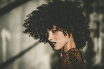 Выразительная девочка с афро стрижка, глядя через плечо на камеру — стоковое фото