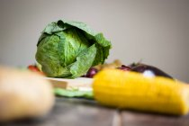Close-up of cabbage and vegetables on grey background — Stock Photo