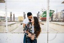 Hugging couple near industrial wharf — Stock Photo