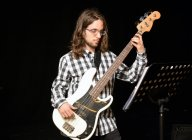 Jeune homme jouant de la basse guitare contre noir — Photo de stock