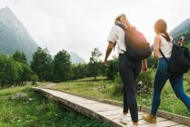 Women walking on wooden path in mountains — Stock Photo