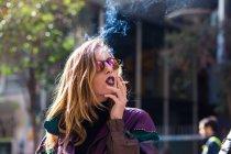 Young girl wearing dark lips smoking on street. — Stock Photo