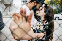 Kissing couple leaning in fence — Stock Photo