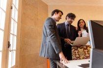 Drei junge Kolleginnen und Kollegen in Anzügen stehen und beobachten in Laptop am Arbeitsplatz — Stockfoto