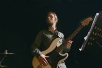 Bass player in stage against black — Stock Photo