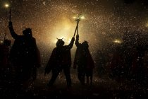Silhouetted people walking with fireworks on streets during festivity. — Stock Photo