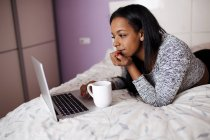 Young girl with cup lying on bed and browsing laptop — Stock Photo