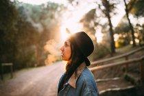 Вид збоку молоду жінку в капелюсі в сонячної дороги в лісі — стокове фото