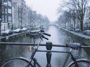 Обтинання велосипедів припаркований на міст над канал Сніжна день міста — стокове фото