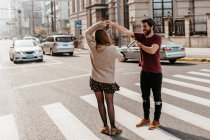 Young cheerful couple dancing on pedestrian crossing. — Stock Photo