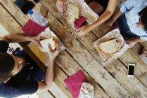 Amis, assis à une table en bois et repas — Photo de stock