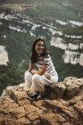 Mujer alegre sentada en piedra y mirando hacia las montañas . - foto de stock