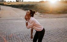 Вид сбоку смеющейся брюнетки в парке — стоковое фото