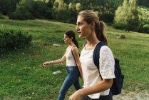 Women walking on lawn — Stock Photo