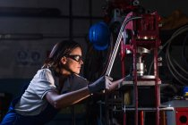 Side view of female mechanic operating hydraulic press — Stock Photo