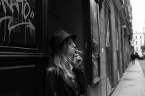 Side view of young stylish girl wearing black hat and leather jacket smoking on street. — Stock Photo