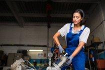Porträt von Brünette weibliche mechanische Befestigung Kompressor-Motor mit Schraubenschlüssel — Stockfoto