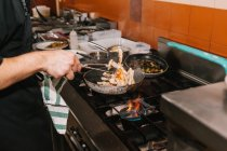 Close up view of chef hands cooking dish on pan at restaurant kitchen — Stock Photo