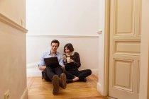 Jeune couple assis sur le sol à la maison et utilisant un ordinateur portable tout en mangeant wok — Photo de stock