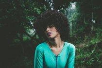 Чуттєвий дівчина з Кучеряве волосся позують над дерев — стокове фото