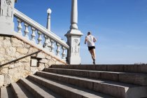 BARCELONA, SPAIN - 17 June, 2011: Back view of man in sportive clothing running up stairs on background of blue sky. — Stock Photo