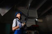 Низький кут портрет жіноче механік операційна підйомник і дивлячись вище — стокове фото